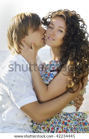 Close-up of a young couple kissing, woman looking to camera - stock photo