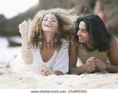 Close-up of a young couple lying on the beach and smiling - stock photo