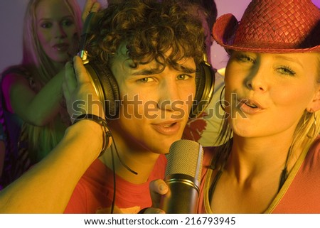 Close-up of a young couple singing in a nightclub - stock photo