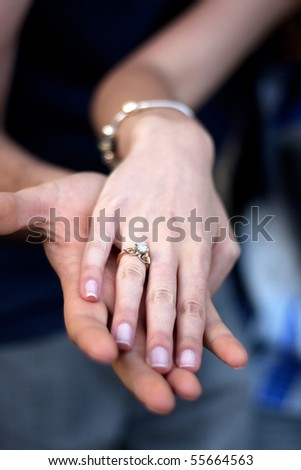 Close up of a young couples hands and diamond engagement ring with platinum and gold accents. Shallow depth of field. - stock photo