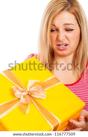 Close up of a young disappointed woman holding yellow gift box, isolated on white background. - stock photo