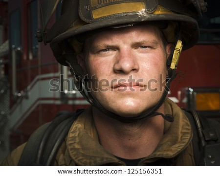 Close-up of a young firefighter wearing hard hat - stock photo