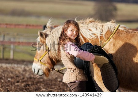Close-up of a young girl carrying saddle to put it on top of her palomino horse - stock photo