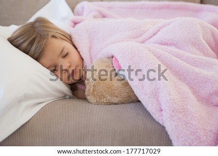Close-up of a young girl sleeping on sofa with stuffed toy in the living room at home - stock photo