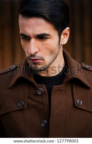 close up of a young handsome man against grunge wooden background. - stock photo