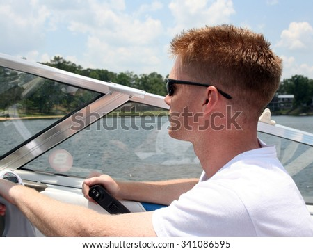 Close up of a young man driving a speedboat with the lake and shoreline in the background - stock photo