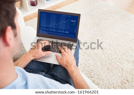 Close-up Of A Young Man Sitting On Couch Using Laptop - stock photo