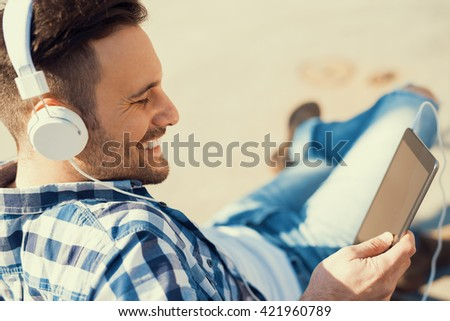Close up of a young man sitting outdoors listening to music