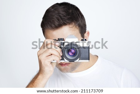 Close-up of a young man using a retro camera against gray background - stock photo