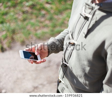Close up of a young man using smartphone - stock photo