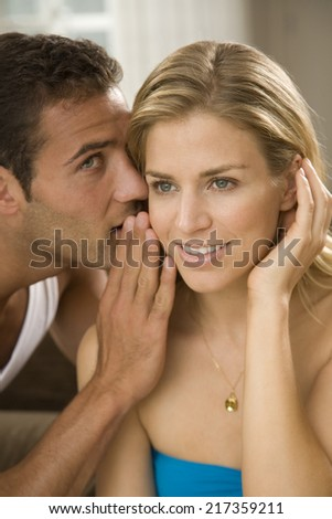 Close-up of a young man whispering to a young woman - stock photo