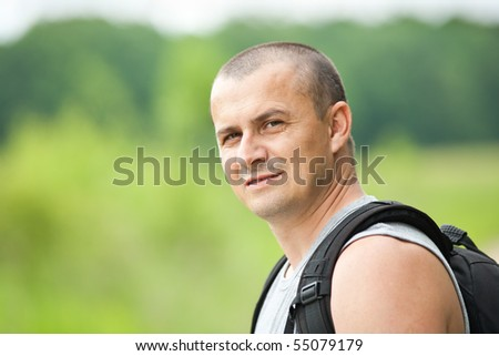 Close up of a young man with backpack and t-shirt hiking into the woods - stock photo