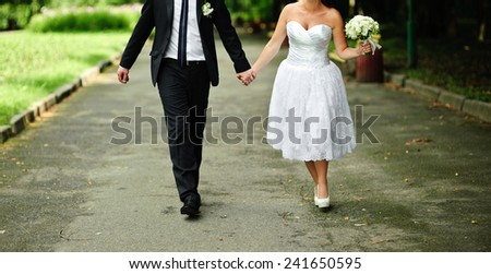 close up of a young newlywed couple with bouquet in the park - stock photo