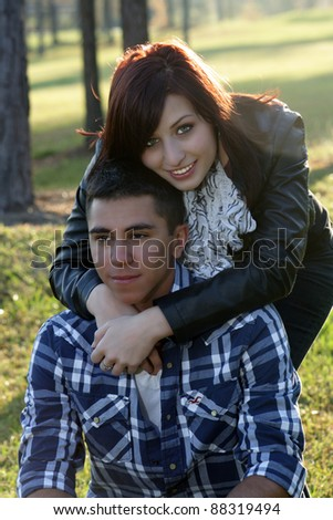 Close-up of a young romantic couple outdoors, backlit by the sun.  Slight lens flare. - stock photo