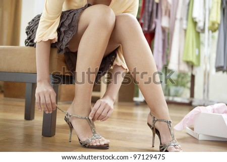 Close up of a young sophisticated woman putting on new shoes in a fashion store.