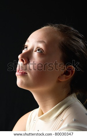 close-up of a young teen girl in profile in a reflective pose as if praying to heaven - stock photo