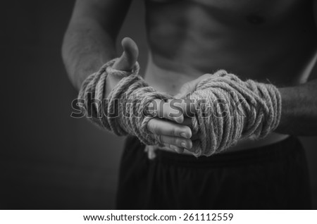 Close-up of a young Thai boxer hands hemp ropes are wrapped before the fight or training. Black and white style - stock photo