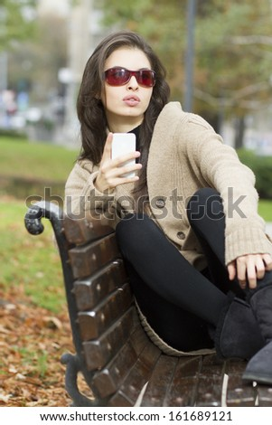 Close up of a young woman a park and typing text message - stock photo