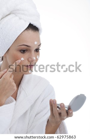 Close-up of a young woman applying moisturizer - stock photo