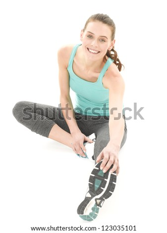 Close-up of a young woman exercising and stretching against white background - stock photo