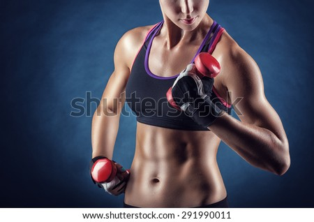 Close-up of a young woman exercising with weights on a dark background - stock photo