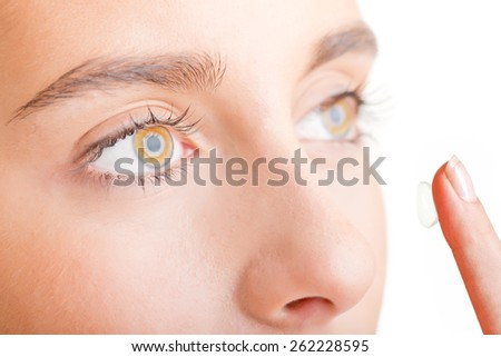 Close up of a young woman face inserting a contact lens, focusing on the eyes, looking away, isolated in white
