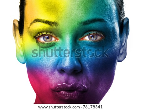 Close up of a young woman face with a rainbow painted on her face - stock photo