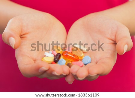 Close up of a young woman hand with pills - stock photo
