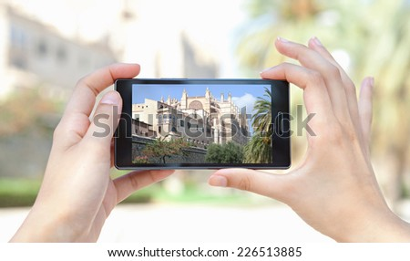Close up of a young woman hands holding a smart digital phone device taking pictures of a characterful architecture cathedral, visiting a destination city on holiday. Vacation technology lifestyle.