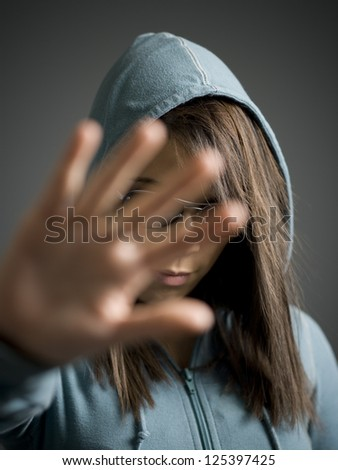 Close-up of a young woman hiding her face - stock photo