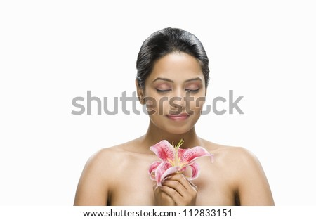Close-up of a young woman holding a flower - stock photo