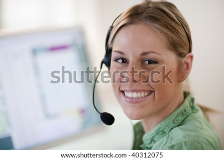 Close-up of a young woman in front of a computer, wearing a headset and smiling at the camera. Horizontal format. - stock photo