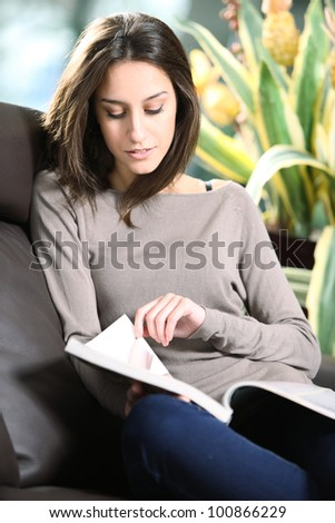 Close-up of a young woman lying on a sofa reading a magazine. - stock photo