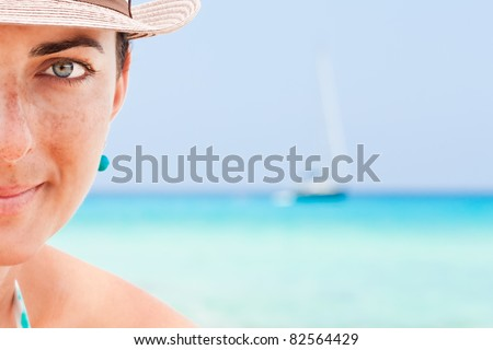 Close-up of a young woman on the beach. - stock photo