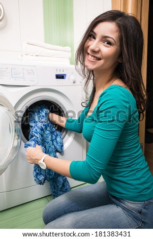 Close up of a young woman putting a cloth into washing machine - stock photo