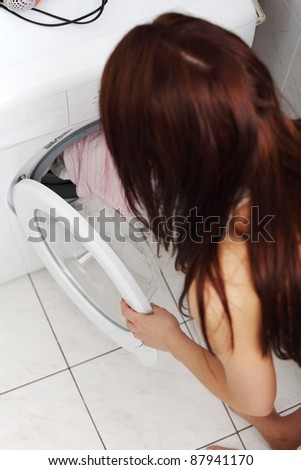 Close up of a young woman putting a cloth into washing machine