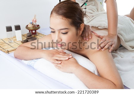Close-up of a young woman receiving back massage at spa - stock photo