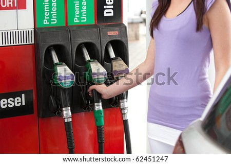 Close-up of a young woman refueling her car in a gas station - stock photo