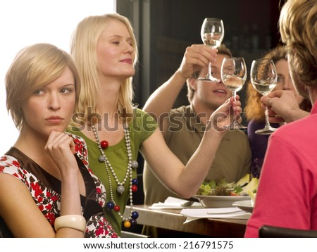 Close-up of a young woman thinking with her hand on her chin and her friends toasting wine glasses in the background