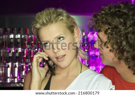 Close-up of a young woman using a mobile phone and a young man looking at her