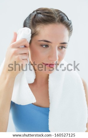 Close-up of a young woman wiping sweat with towel