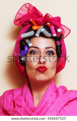 Close-up of a young woman with hair curlers giving a kiss