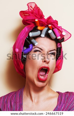 Close-up of a young woman with hair curlers making a yelling grimace