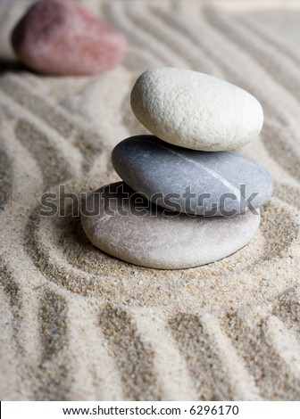 Close up of a zen rock garden with a pile of stones in sand. - stock photo