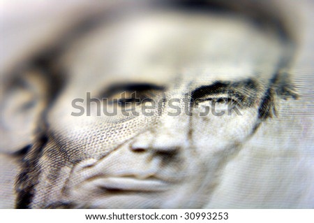 Close up of Abe Lincoln on five dollar bill - stock photo