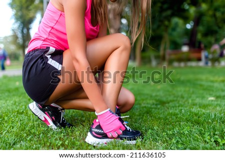 Close-up of active jogging female runner, preparing shoes for training and working out at fitness park - stock photo