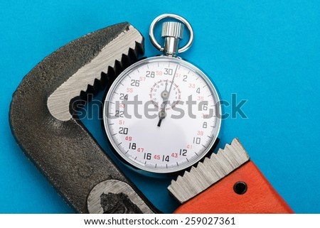 Close-up Of Adjustable Wrench And Stopwatch Over Blue Background - stock photo