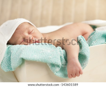 Close-up of adorable newborn baby sleeping in a wooden case - stock photo