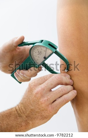 Close-up of adult male hand using caliper to test body fat. - stock photo