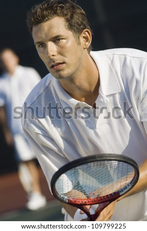 Close-up of adult man holding racket with partner in the background